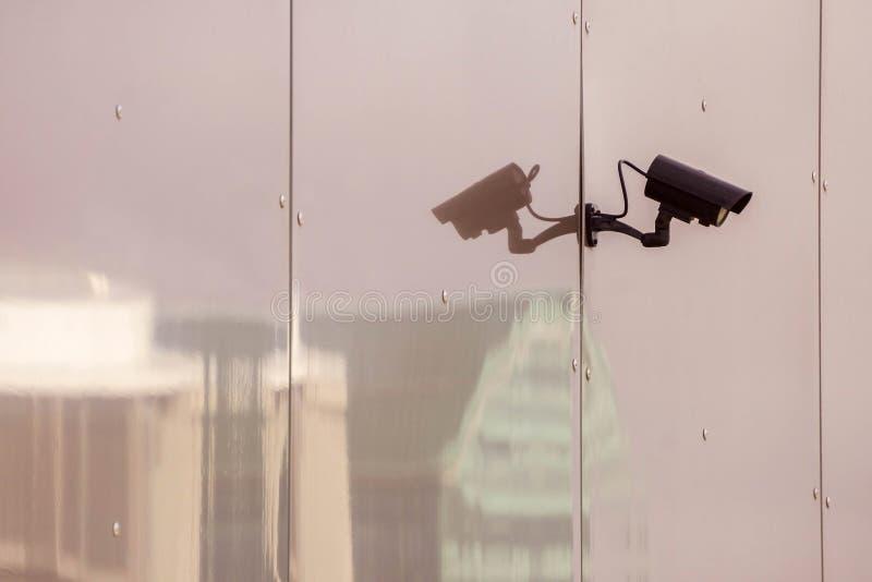 Macchina fotografica del CCTV sulla parete di vetro tonificata di una costruzione con la riflessione delle costruzioni moderne de fotografia stock libera da diritti