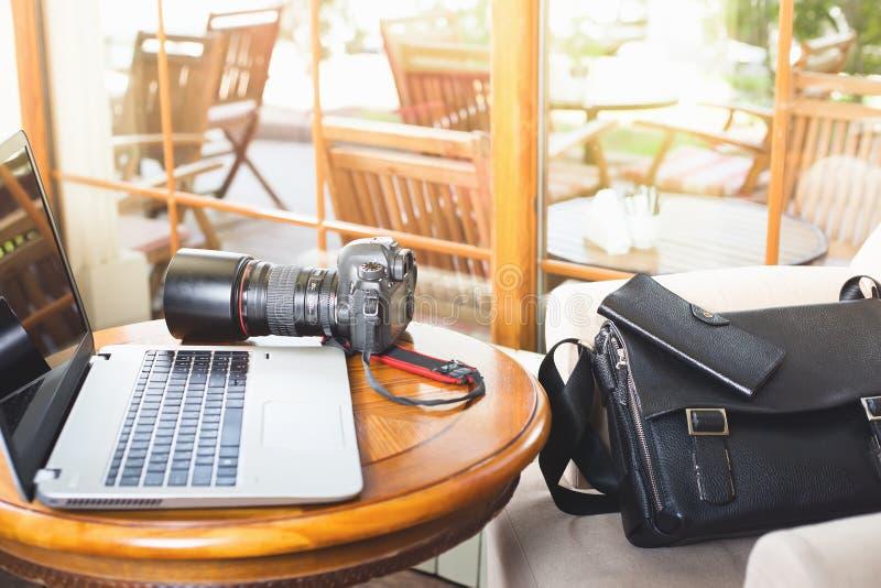Macchina fotografica del dslr e del computer portatile al caffè fotografia stock libera da diritti