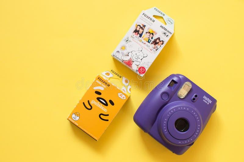 Macchina fotografica del instax di Fujifilm mini e gudetama e film istantaneo di Winnie the Pooh su fondo giallo fotografia stock