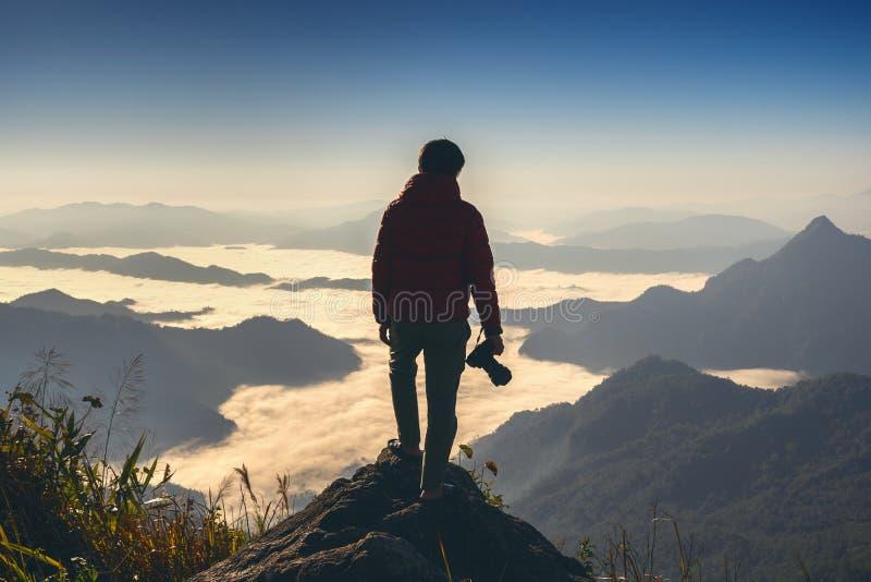 Macchina fotografica della tenuta della mano del fotografo e stare sopra la roccia in natura concetto di corsa immagini stock