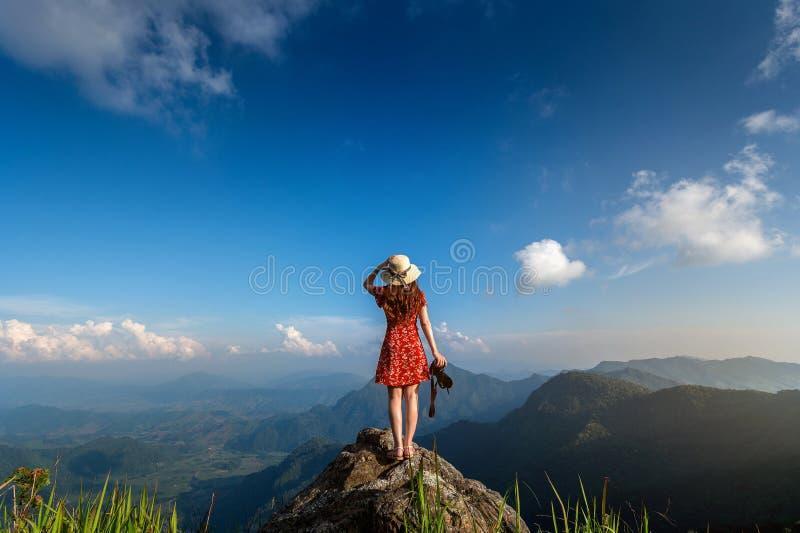Macchina fotografica della tenuta della mano della donna e condizione sopra la roccia in natura concetto di corsa fotografia stock