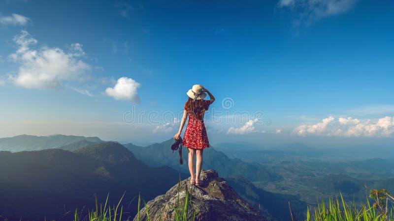 Macchina fotografica della tenuta della mano della donna e condizione sopra la roccia in natura concetto di corsa Tono d'annata fotografie stock libere da diritti