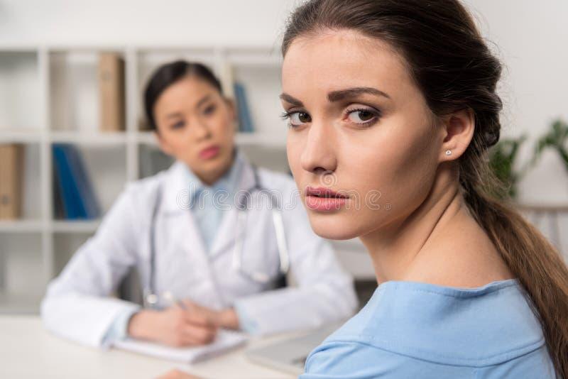 Macchina fotografica di sguardo paziente turbata con medico che si siede nel luogo di lavoro dietro fotografia stock