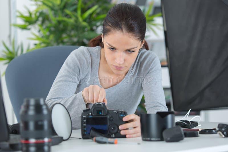 Macchina fotografica di smontaggio della foto del fotografo femminile nel luogo di lavoro fotografia stock libera da diritti