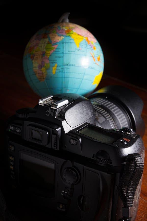 Macchina fotografica digitale con il globo immagini stock