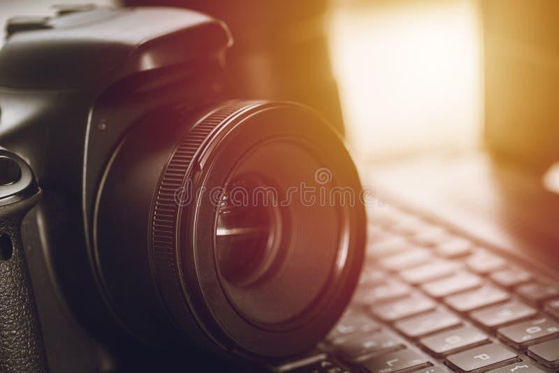 Macchina fotografica digitale DSLR del primo piano con la lente della correzione sulla tastiera del computer portatile del comput immagini stock libere da diritti