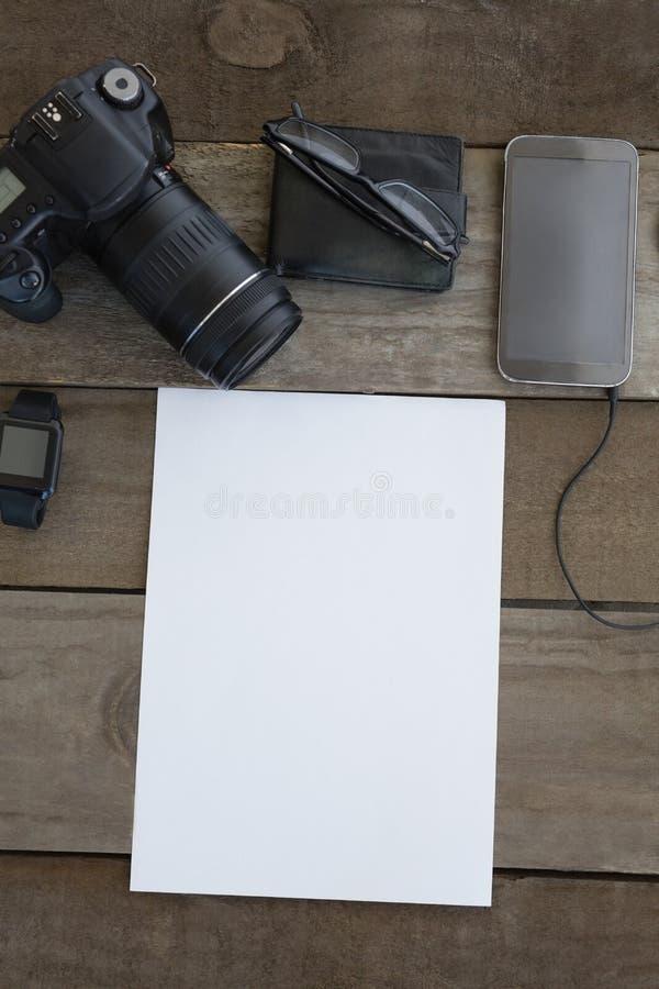 Macchina fotografica digitale, portafoglio, occhiali, smartwatch, telefono cellulare e carta in bianco su superficie di legno fotografia stock