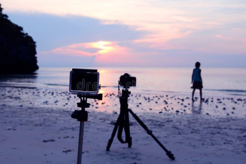 Macchina fotografica e treppiede alla spiaggia con un'immagine di sfondo della ragazza immagine stock