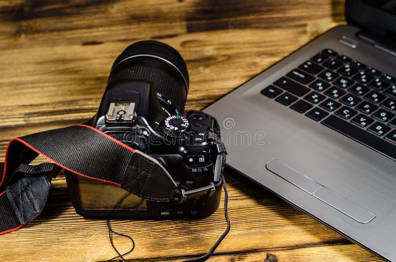 Macchina fotografica moderna e computer portatile di DSLR sulla tavola di legno fotografia stock libera da diritti