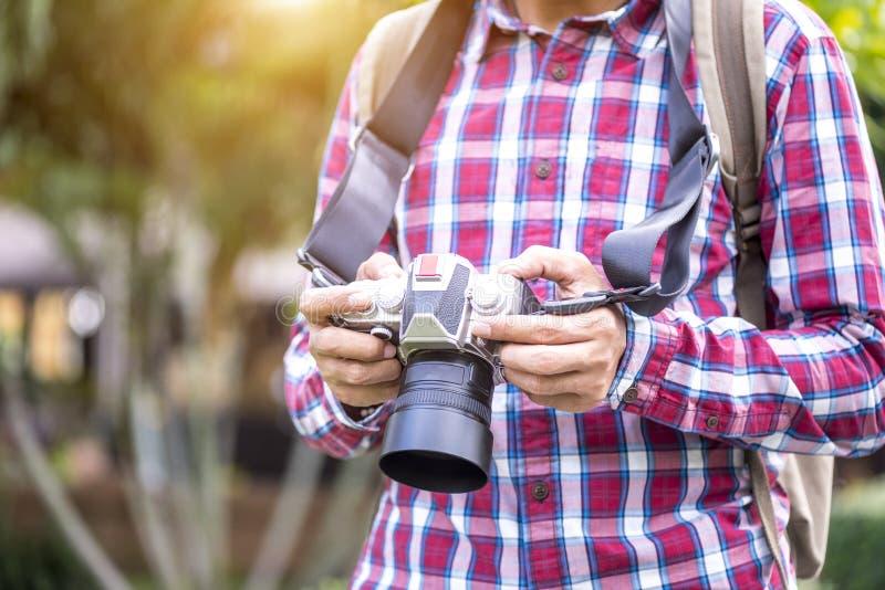 Macchina fotografica professionale della tenuta del fotografo sulle mani fotografia stock