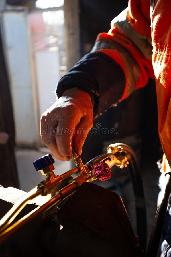 Macchina ossitaglio di riparazione e di pulizia nella sua officina, fuoco selettivo dell'uomo fotografie stock