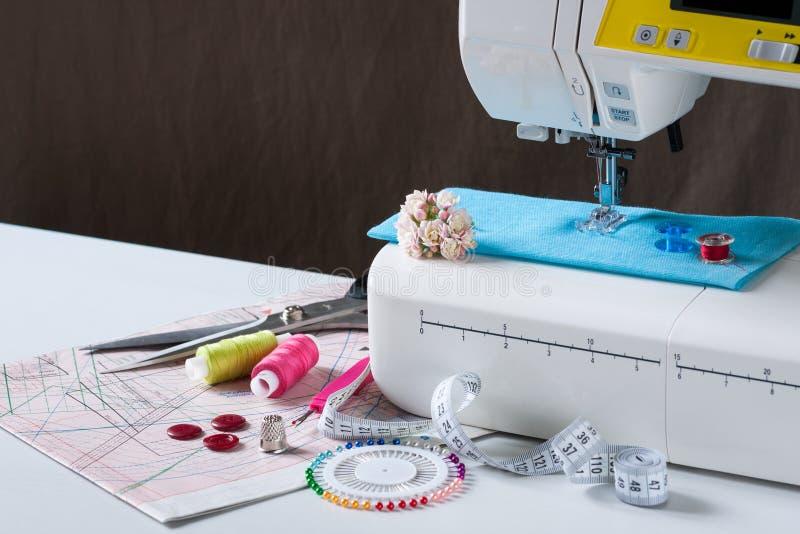Macchina per cucire con differenti accessori sulla Tabella bianca fotografia stock