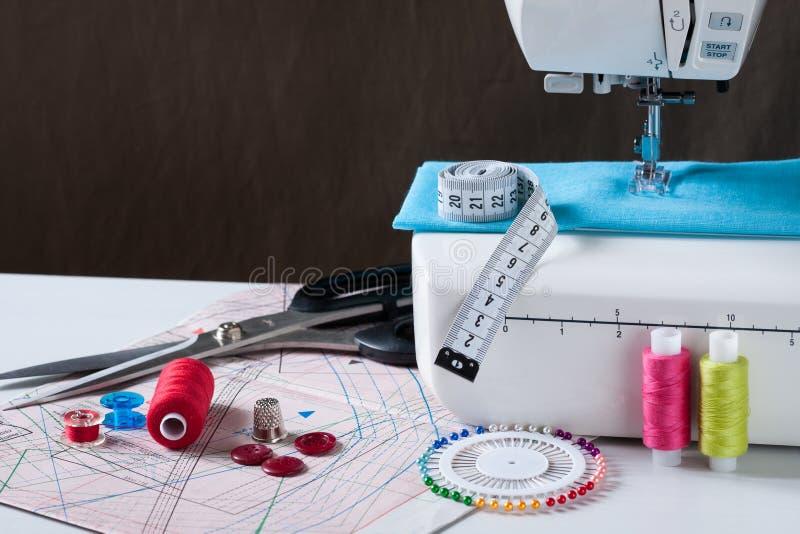Macchina per cucire con differenti accessori sulla Tabella bianca immagini stock libere da diritti