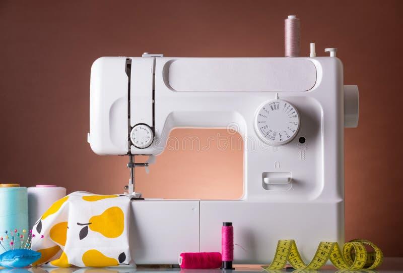 Macchina per cucire della famiglia, accessori, tessuto al di sotto del piede del presser immagini stock libere da diritti