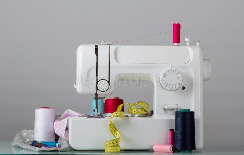 Macchina per cucire elettrica della famiglia e rifornimenti di cucito, su grey fotografia stock