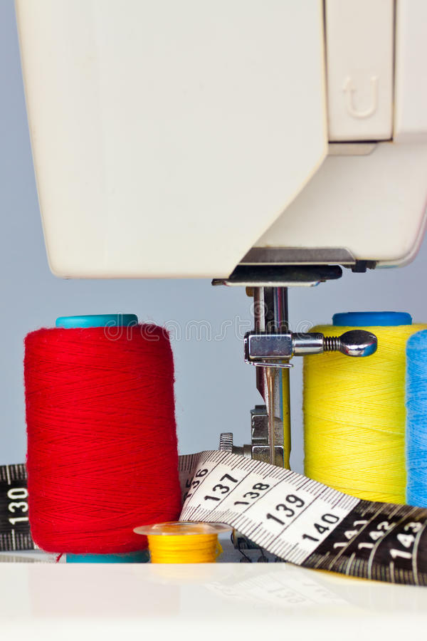Macchina per cucire, nastro di misurazione e bobine del filetto fotografia stock