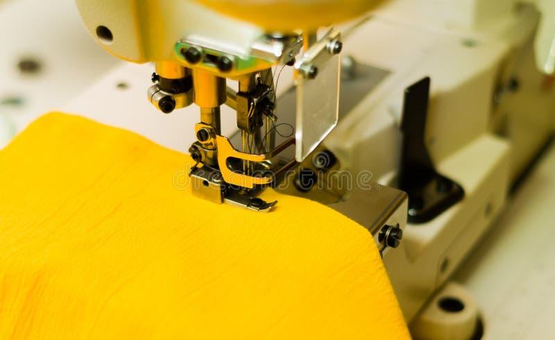Macchina per cucire pronta ad iniziare con tessuto giallo, attrezzatura d'acciaio fotografia stock libera da diritti