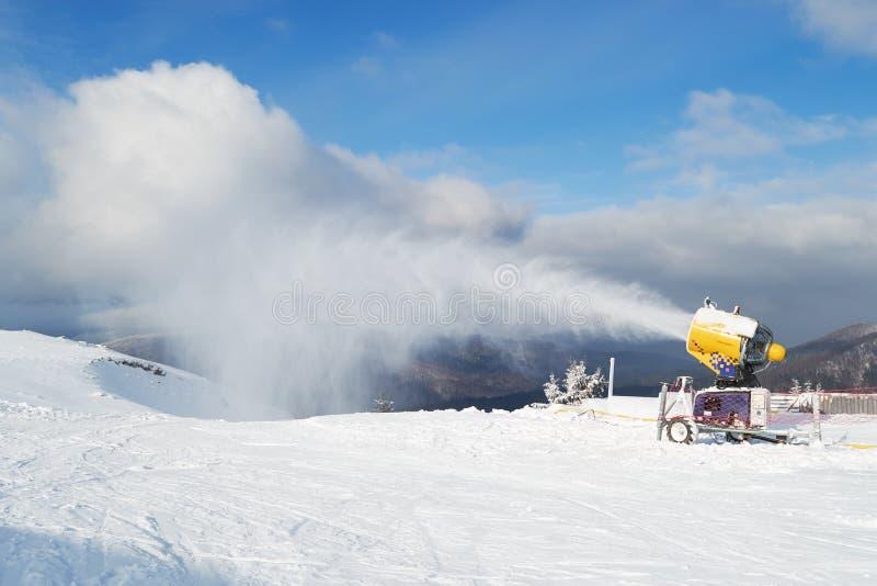 Macchina per lavare i cannoni con neve artificiale su un dominio Azuga ski, regione della Valle di Prahova, Romania, durante la b fotografia stock libera da diritti