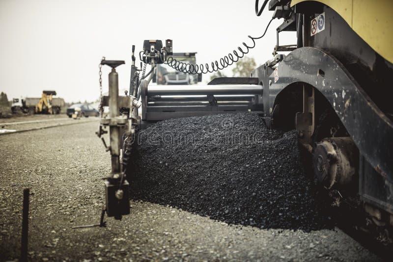 Macchinario che pone asfalto o bitume fresco durante la costruzione di strade sul cantiere annata, retro effetto sulla foto immagini stock