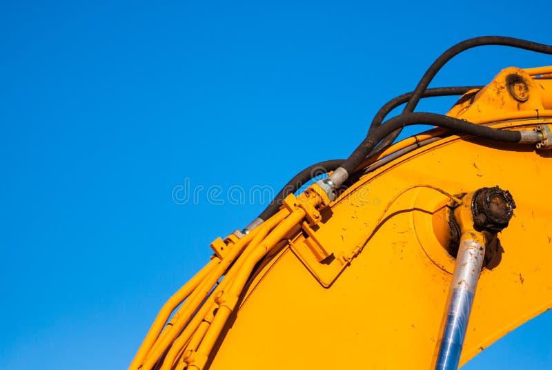 Macchinario giallo e l'idraulica su cielo blu immagine stock