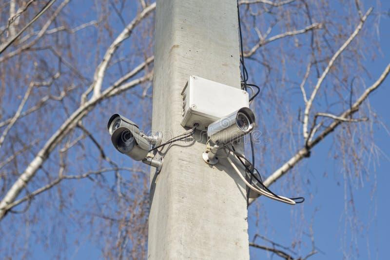 Macchine fotografiche di videosorveglianza compatte sulla posta di sostegno nelle aree pubbliche su cielo blu Videocamere di sicu fotografia stock