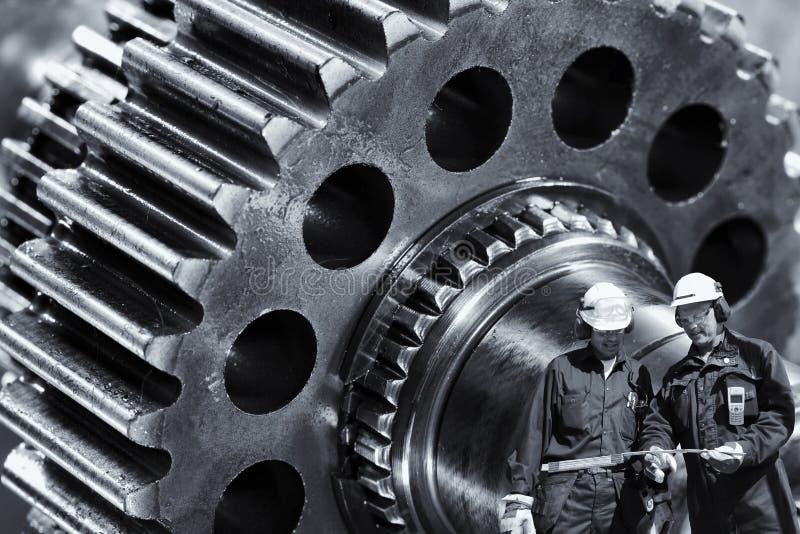 Macchinisti, ingegneri con il macchinario gigante delle ruote dentate fotografia stock libera da diritti