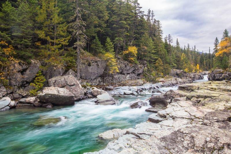 Macdonald creek in Glacier National Park. Beautiful turquoise blue water flowing in McDonald Creek in Glacier National Park, Montana, USA stock photography