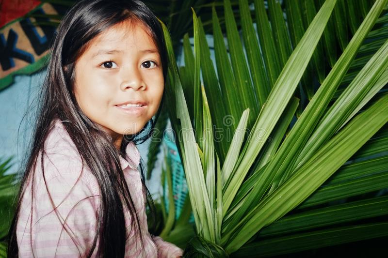 Young girl preparing for a village event making palm leaf decoration royalty free stock photography