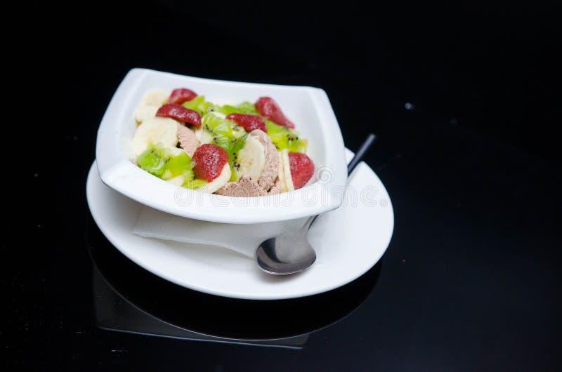 Macedonia con il gelato in piatto bianco fotografia stock