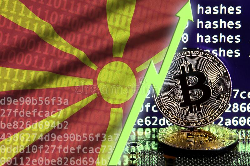 Macedonia flag and rising green arrow on bitcoin mining screen and two physical golden bitcoins royalty free stock photo