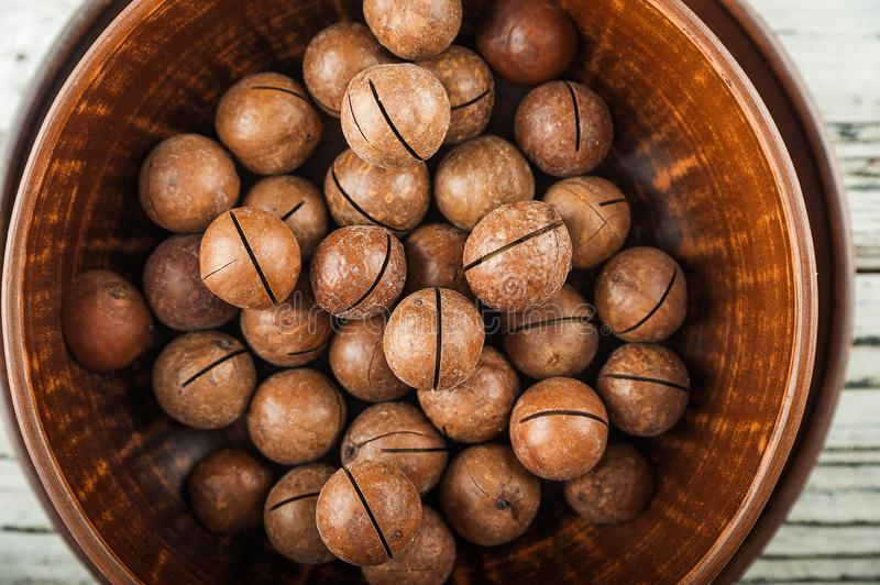 Macedonian nuts on a wooden plate on the background of a textural wooden table. Macedonian nuts closeup and copy space royalty free stock image