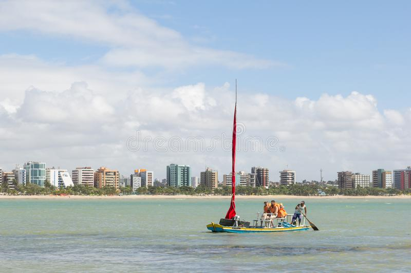 Maceio, Brazil - September, 04 2017. Couple of tourists is doing. Traditional raft ride on the beach of Pajucara. they will visit the natural pools at low tide royalty free stock photos