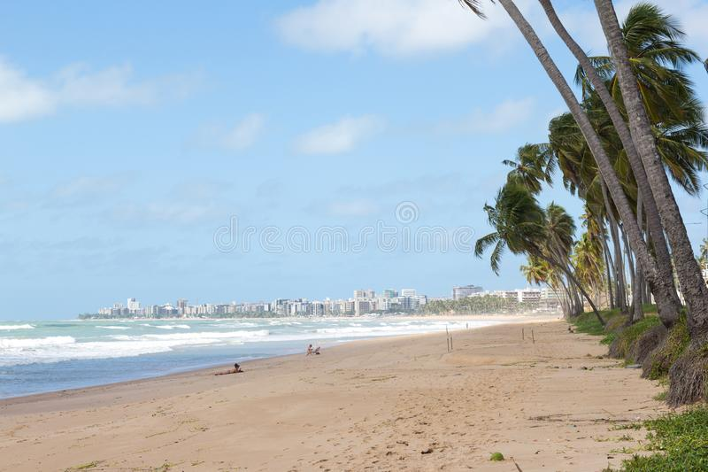 Maceio, Brazil - September, 05 2017. Cruz das Almas beach almost. Deserted. Coconut trees and the city in the background royalty free stock images