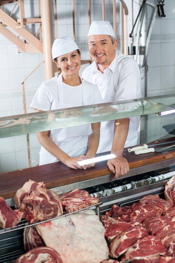 Macellai che stanno al contatore di carne in negozio immagini stock libere da diritti