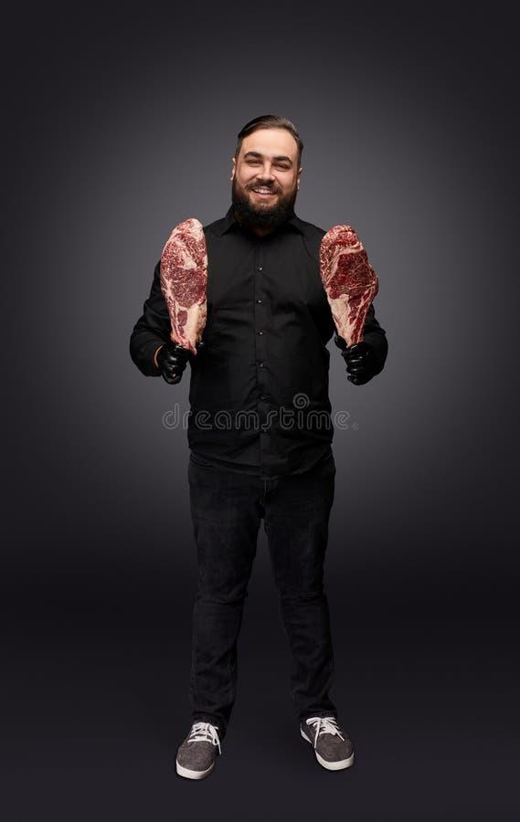 Macellaio alla moda che posa con la carne fotografie stock libere da diritti