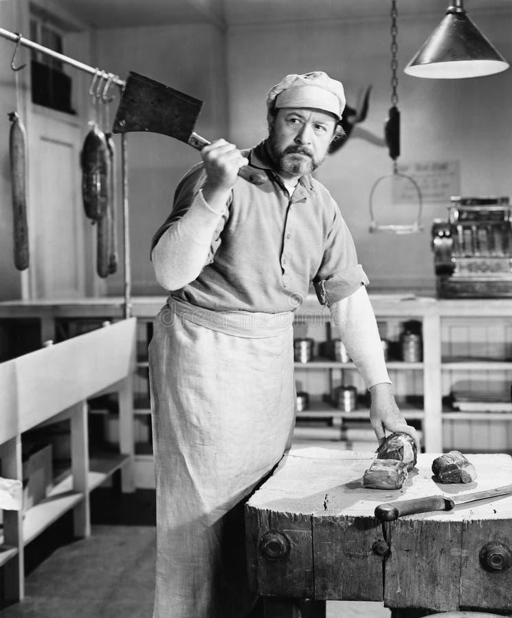 Macellaio che taglia carne a pezzi con la mannaia (tutte le persone rappresentate non sono vivente più lungo e nessuna proprietà  immagine stock libera da diritti