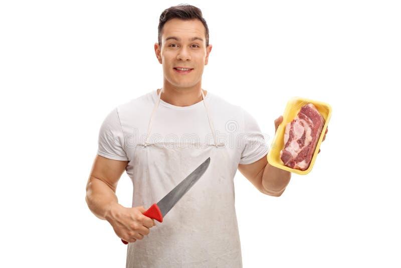 Macellaio che tiene un coltello e una bistecca fotografie stock