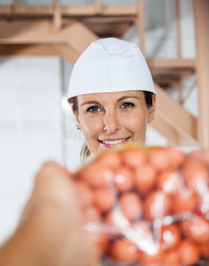 Macellaio felice Selling Packed Sausages al cliente immagine stock libera da diritti