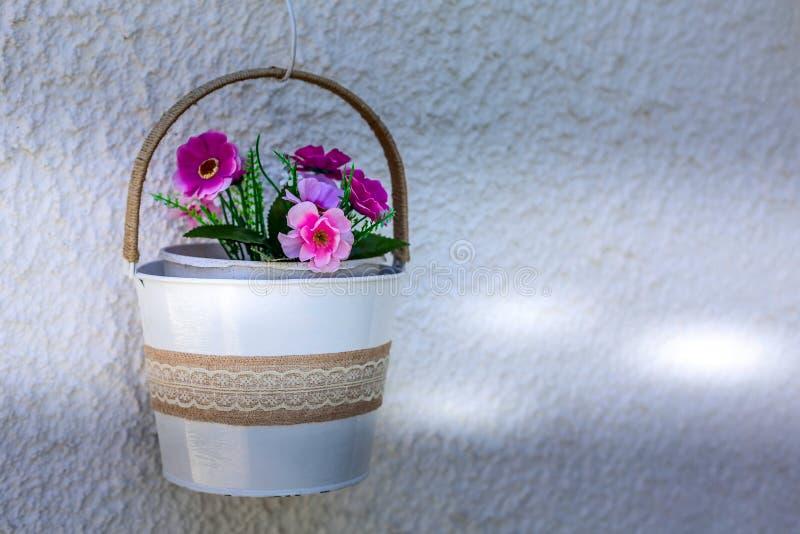 Maceta colgante con las plantas rosadas en la pared blanca imágenes de archivo libres de regalías