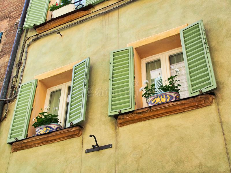 Macetas coloridas en Pale Green Shuttered Windows, Siena, Italia imagen de archivo