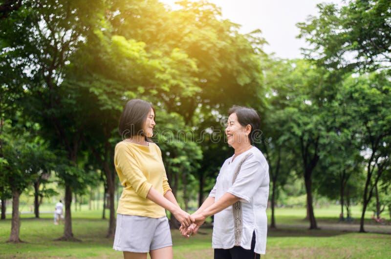 Mach's gut und Stützkonzept, Porträt der älteren asiatischen Frau mit der Tochterhand, die über Park zusammenhält und lacht, glüc stockbild