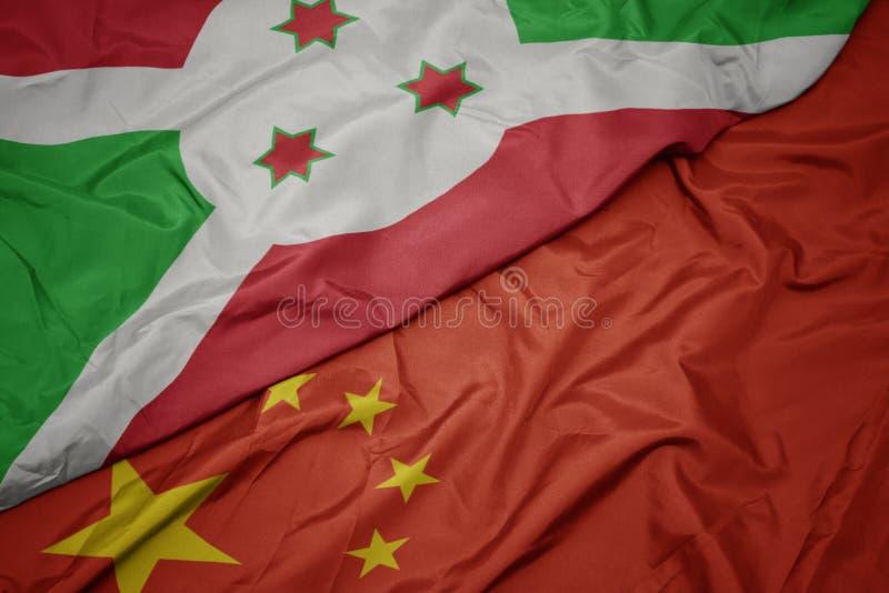 machać kolorową flagę porcelana i flagę państowową Burundi zdjęcia stock