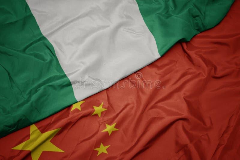 machać kolorową flagę porcelana i flagę państowową Nigeria zdjęcia stock