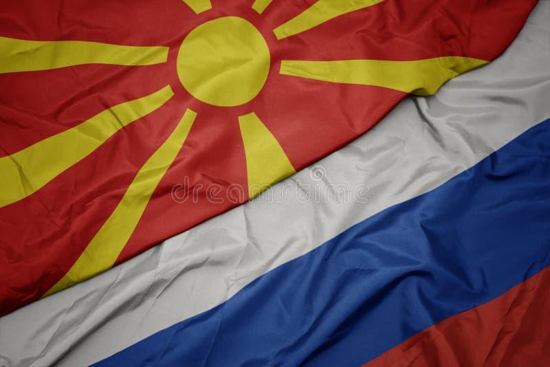 machać kolorową flagę Russia i flagę państowową Macedonia obrazy stock