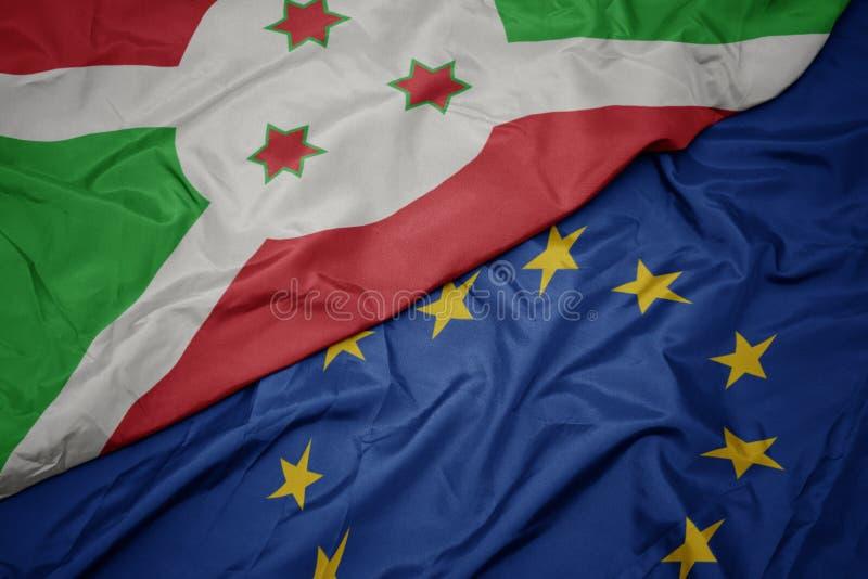 machać kolorową flagę unia europejska i flagę Burundi zdjęcie royalty free