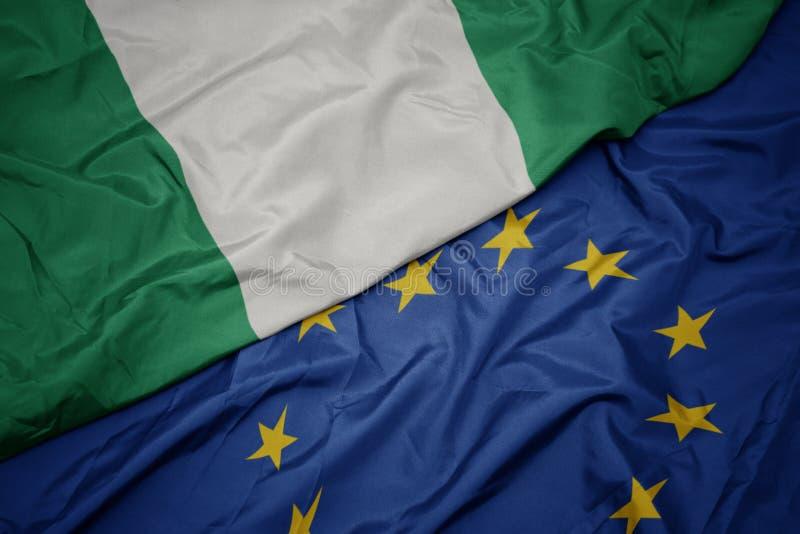 machać kolorową flagę unia europejska i flagę Nigeria zdjęcie stock