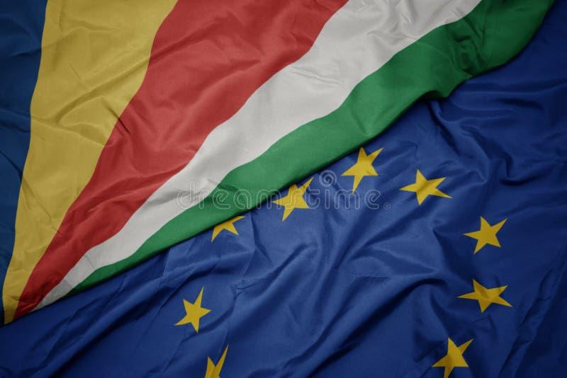machać kolorową flagę unia europejska i flagę Seychelles obrazy stock
