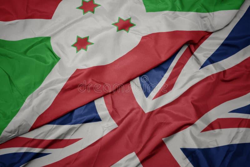 machać kolorową flagę wielki Britain i flagę państowową Burundi fotografia royalty free