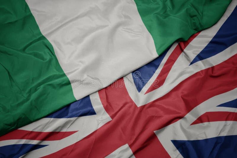 machać kolorową flagę wielki Britain i flagę państowową Nigeria fotografia royalty free