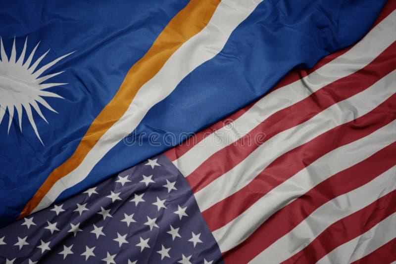 machać kolorową flagę zlani stany America i flaga państowowa Marshall wyspy fotografia stock